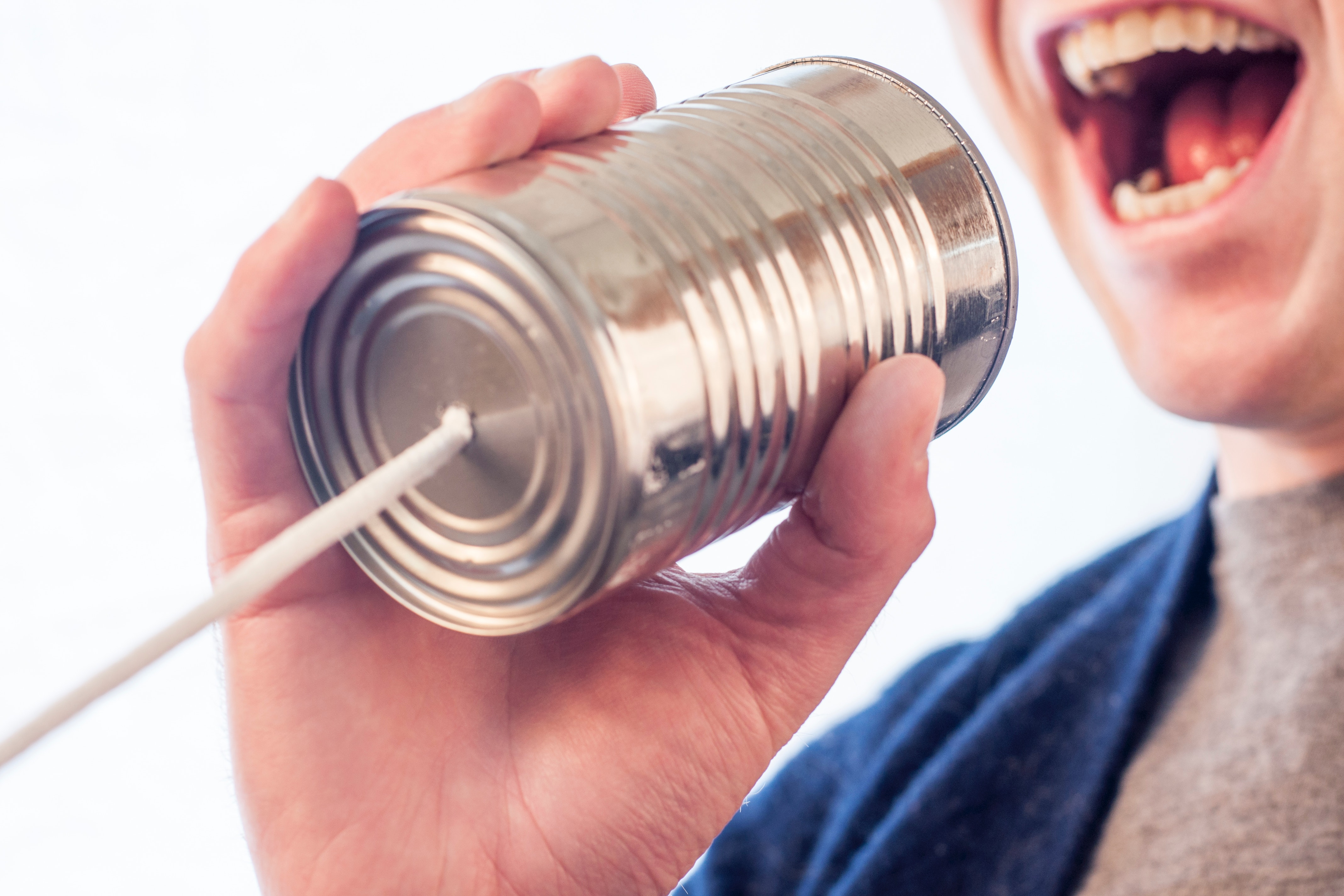 picture of person speaking into a can with a string attached